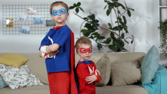 Little Boy and Girl in Superhero Costumes Posing for Camera Confident girl and her cute little brother in superhero costumes standing back to back with arms crossed, looking at camera and stamping their feet while posing in kids room at home mask disguise stock videos & royalty-free footage