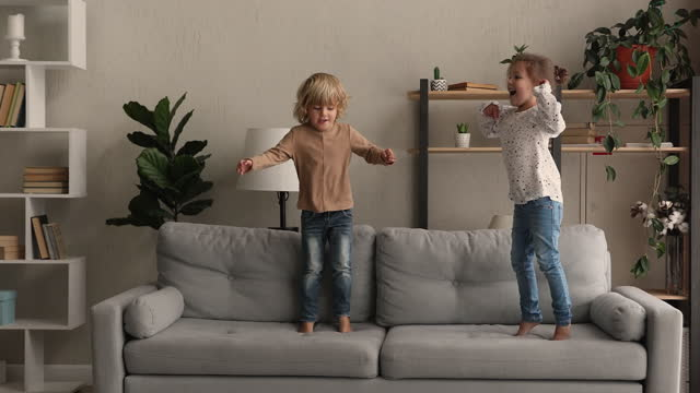 Little boy and girl jumping on couch at home