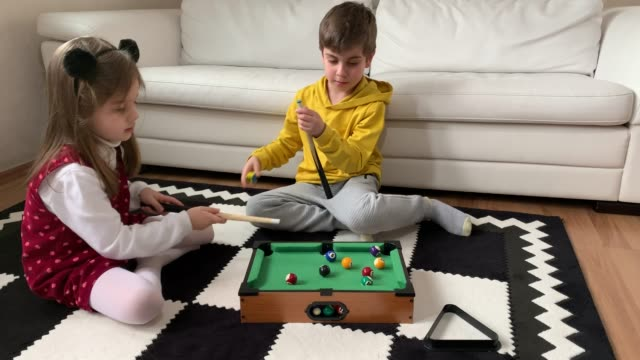 A little boy and girl playing billiards at home