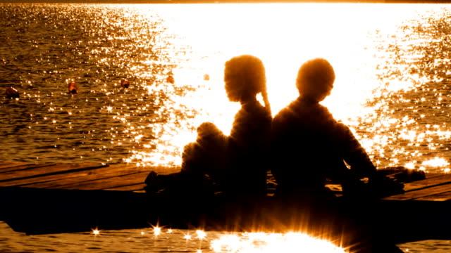 kleine jungen und mädchen sitzen auf der brücke bei sonnenuntergang - rücken an rücken stock-videos und b-roll-filmmaterial