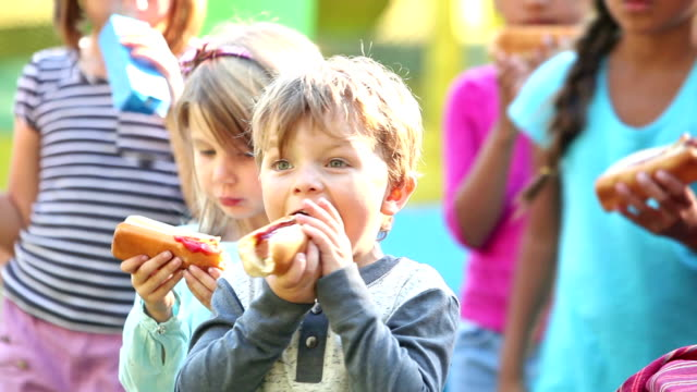 Little boy and group of children eating hotdogs A group of five multiracial children standing outdoors eating hotdogs. The focus is on the little boy, front and center, taking bites and then wiping his face with his sleeve. hot dog stock videos & royalty-free footage