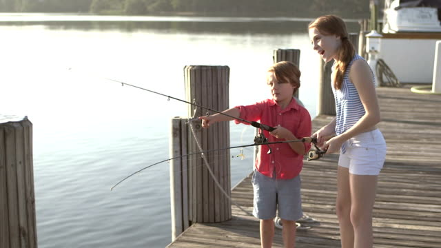 Little boy and his big sister with fishing rods on dock video