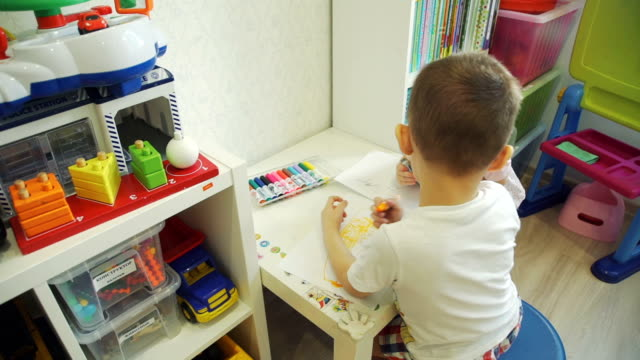 Little Boy and his Cute Sister Drawing at Home Little Boy and his Cute Little Sister Drawing with Felt-tip Pens in Nursery Room playroom stock videos & royalty-free footage