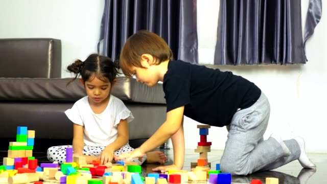 Little boy and little girl play wooden toys blocks on the floor, building towers at home