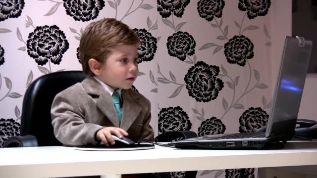 vidéos et rushes de petit garçon et bureau - costume habillé
