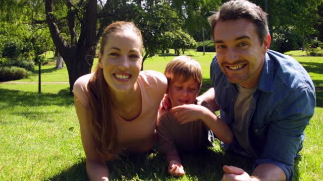mały chłopiec i rodziców w uśmiech na aparat w parku - 30 39 lat filmów i materiałów b-roll
