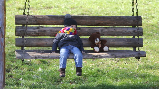 Little boy and teddy bear relax on balancing chair in park, beautiful spring day Little boy and teddy bear relax on balancing chair in park, beautiful spring day rocking chair stock videos & royalty-free footage