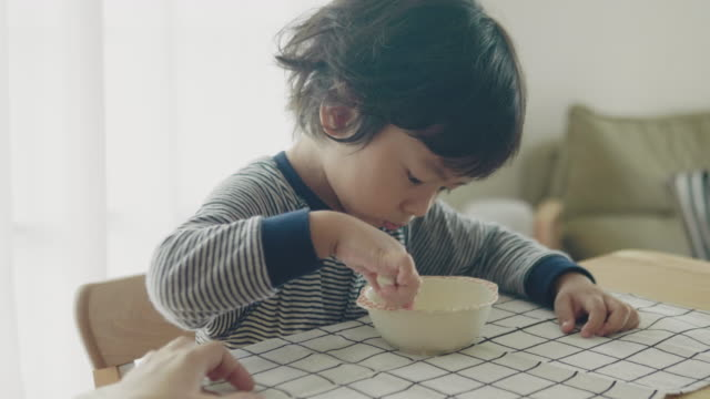 Little Boy At Home Eating Breakfast In Kitchen Together