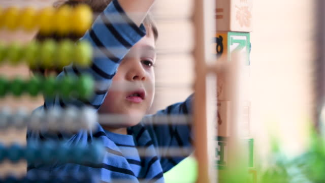 Little boy at pre school classroom learning how to count using a colorful abacus (picture taken in a real US classroom)