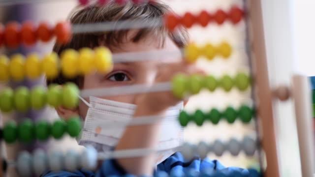 liten pojke på förskolan klassrummet bär en skyddande ansiktsmask (bild tagen i en riktig amerikansk klassrum) - abakus bildbanksvideor och videomaterial från bakom kulisserna