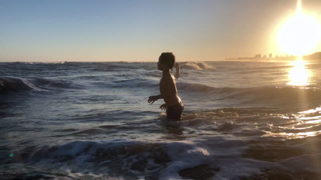 Little boy at the beach playing silhouette of child playing with beach waves