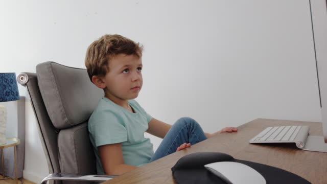 vídeos de stock, filmes e b-roll de garotinho frequentando aula online durante quarentena epidêmica de coronavirus - salas de aula