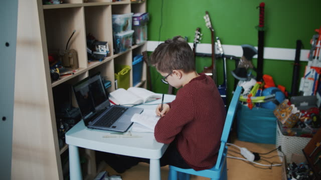 vídeos de stock e filmes b-roll de little boy attending to online school class from his room. - isolado