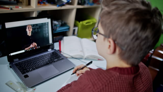 Little boy attending to online school class from his room.