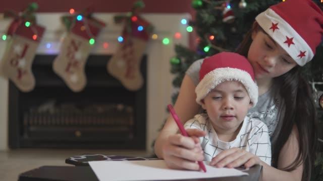 vídeos de stock, filmes e b-roll de garotinho, sendo ajudado por sua irmã mais velha para escrever uma carta para o papai noel - correio correspondência
