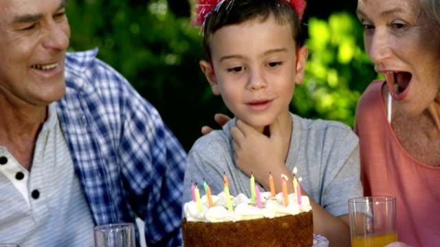 vidéos et rushes de un petit garçon souffle les bougies - fête de naissance