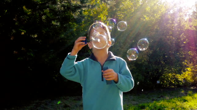 Little boy blowing up the soap bubbles  in autumn forest video