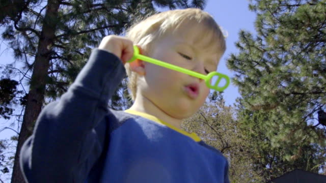 Little boy blows bubbles using wand video