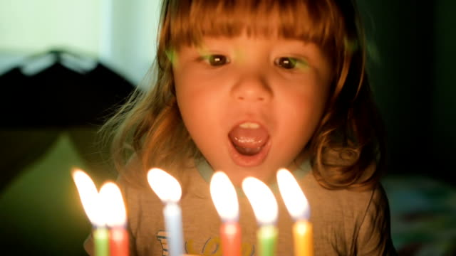 Little boy blows out candles on birthday cake at party. Closeup. Slow motion. video