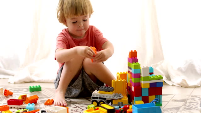 Little boy builds colored blocks Little boy builds a toy house of colored blocks sitting on a white background brick stock videos & royalty-free footage