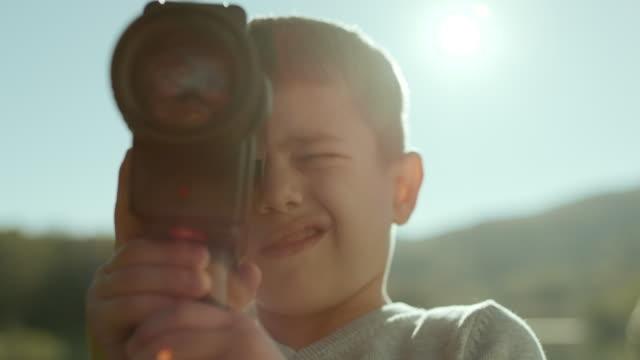 liten pojke fånga ögonblicket med sin kamera - filma bildbanksvideor och videomaterial från bakom kulisserna
