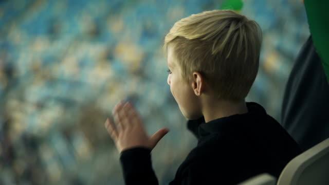 Menino cantando e acenando a bandeira do Brasil para apoiar o time de futebol, fã - vídeo