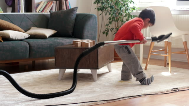 Little boy cleaning floor with vacuum cleaner Little boy cleaning floor with vacuum cleaner chores stock videos & royalty-free footage