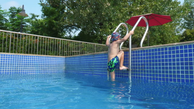 little boy climb out of swimming pool,4k - solo bambini maschi video stock e b–roll