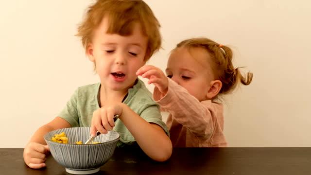 朝食中に気まぐれな妹と通信する小さな男の子 - 兄弟姉妹点の映像素材/bロール