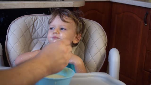 little boy dad feeds the porridge for breakfast video