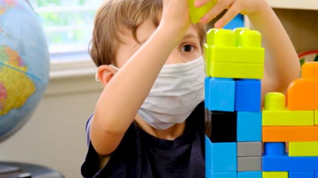 vídeos y material grabado en eventos de stock de pequeño escritorio de niño en la escuela preescolar jugando con una máscara protectora de la cara - cuidado infantil