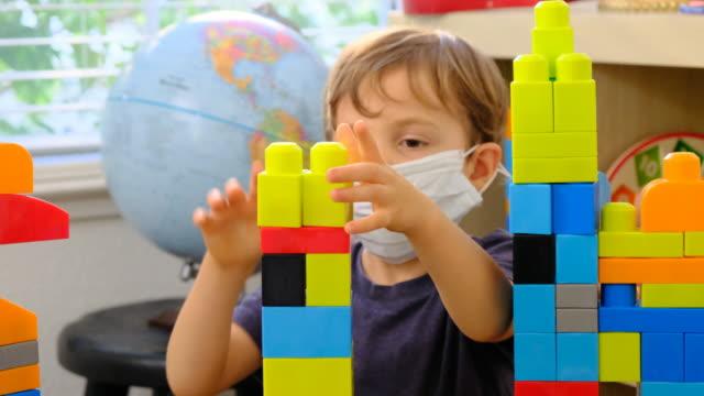 scrivania per bambini alla scuola materna che gioca indossando una maschera protettiva per il viso - studio camera video stock e b–roll