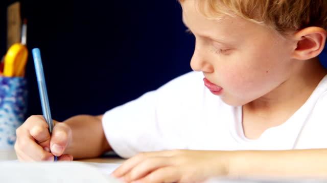 Petit garçon écrit avec diligence ses devoirs - Vidéo