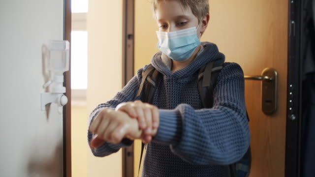 Little boy disinfecting hands after returning from school