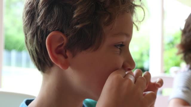kleiner junge tun digust gesicht und lustige grimasse und dann einen biss von essen - ekel stock-videos und b-roll-filmmaterial