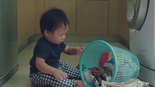 家庭での洗濯をして小さな男の子 - 家の雑用点の映像素材/bロール