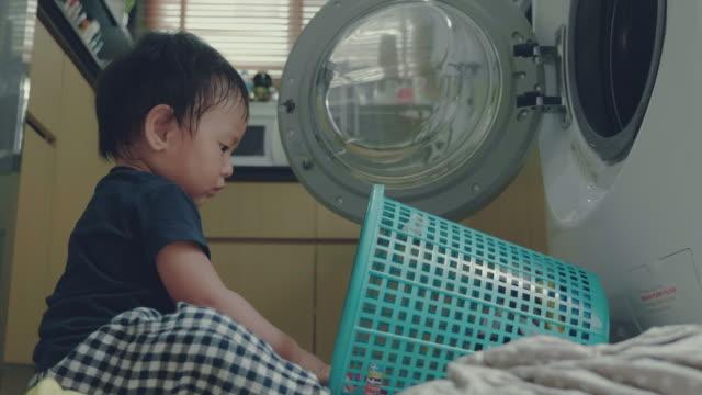 家庭での洗濯をして小さな男の子 - 楽しい 洗濯点の映像素材/bロール