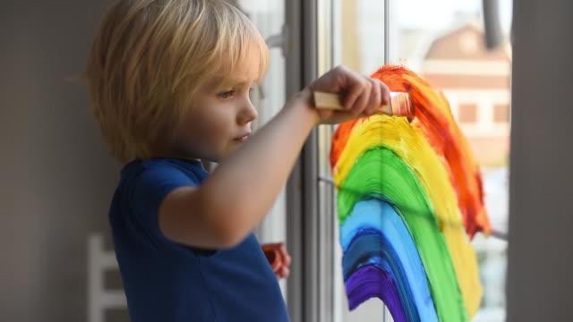 kleiner junge zeichnung auf fenster regenbogen während coronavirus quarantäne. regenbogen-zeichen ist symbol der hoffnung, bedeutet, dass alles in ordnung sein wird. - krankheitsverhinderung stock-videos und b-roll-filmmaterial