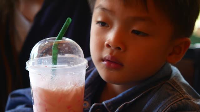 kleiner Junge Saft durch einen Strohhalm zu trinken – Video