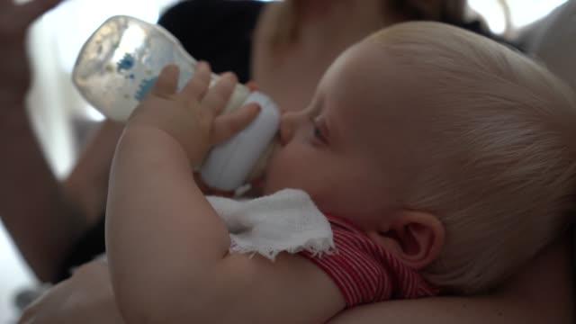 bambino che beve latte con bottiglia per bambini - neonati maschi video stock e b–roll
