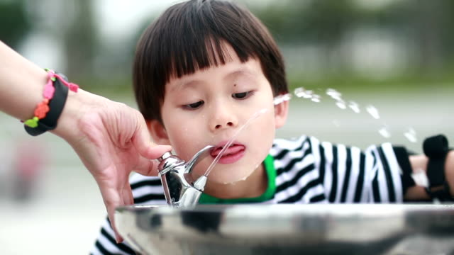 little boy drinking tap water - fontana struttura costruita dall'uomo video stock e b–roll