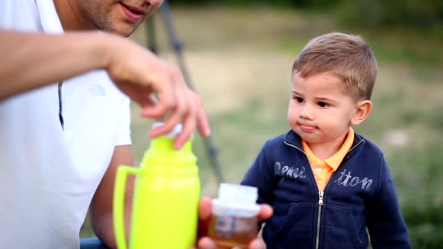 Little boy drinks water from a baby bottle video