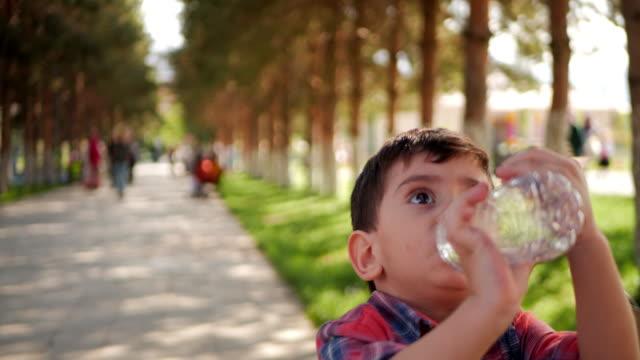 Little boy drinks water from plastic bottle in the park.