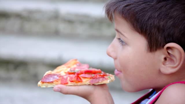 vídeos de stock, filmes e b-roll de menino comendo uma fatia de pizza - fatia