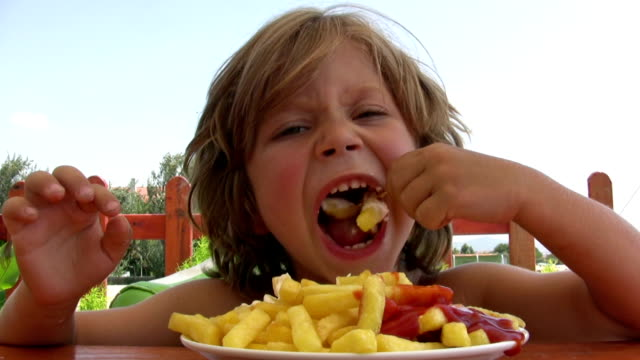 ragazzino mangiare patatine fritte - patate video stock e b–roll