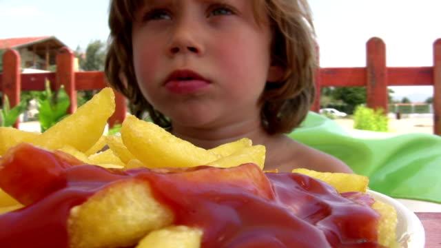 ragazzino mangiare patatine fritte - ketchup video stock e b–roll