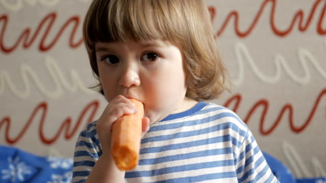 Little boy eating healthy food vegetable, carrot Little boy eating healthy food vegetable, carrot carrot stock videos & royalty-free footage