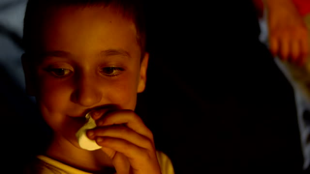 HD: Little Boy Eating Marshmallow HD1080p: Close up shot of a little boy eating a marshmallow by the campfire. marshmallow stock videos & royalty-free footage