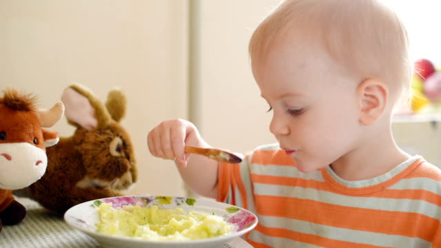 Little boy eating mashed potatoes Little boy sitting at dining table and eating mashed potatoes using a wooden spoon kitchen utensil stock videos & royalty-free footage