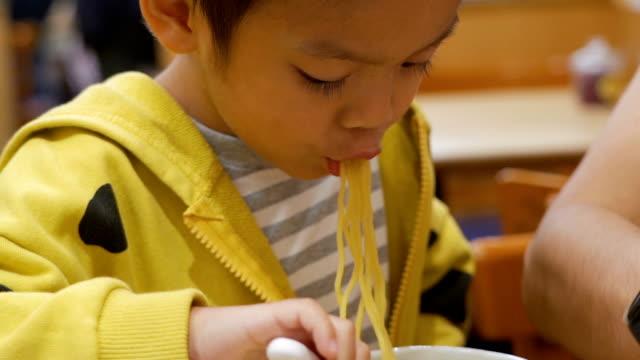 kleiner junge, der nudel im japanischen restaurant isst. - 2 3 jahre stock-videos und b-roll-filmmaterial